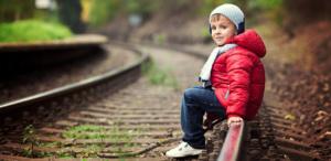 Мальчик на железнодорожных путях в демисезонной куртке